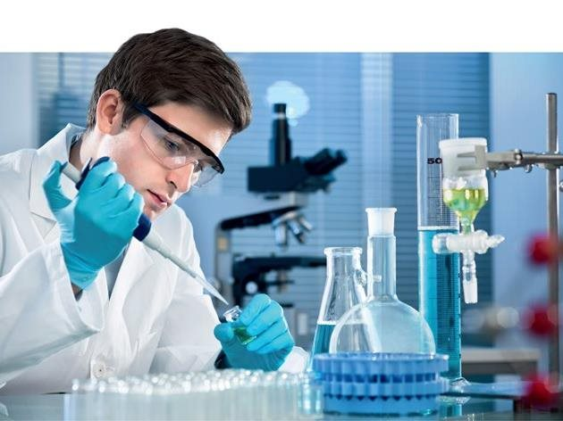 guy with glasses working with pipe in a chemical laboratory