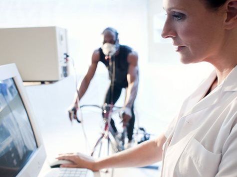 woman doctor monitoring value of a man cycling