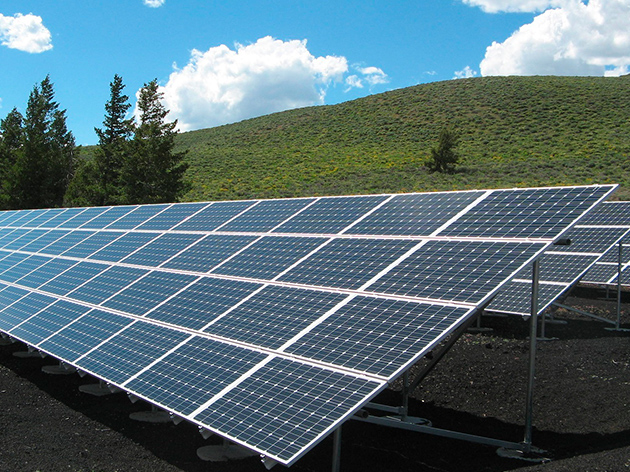 Solar panels on blue cloudy sky and green hills